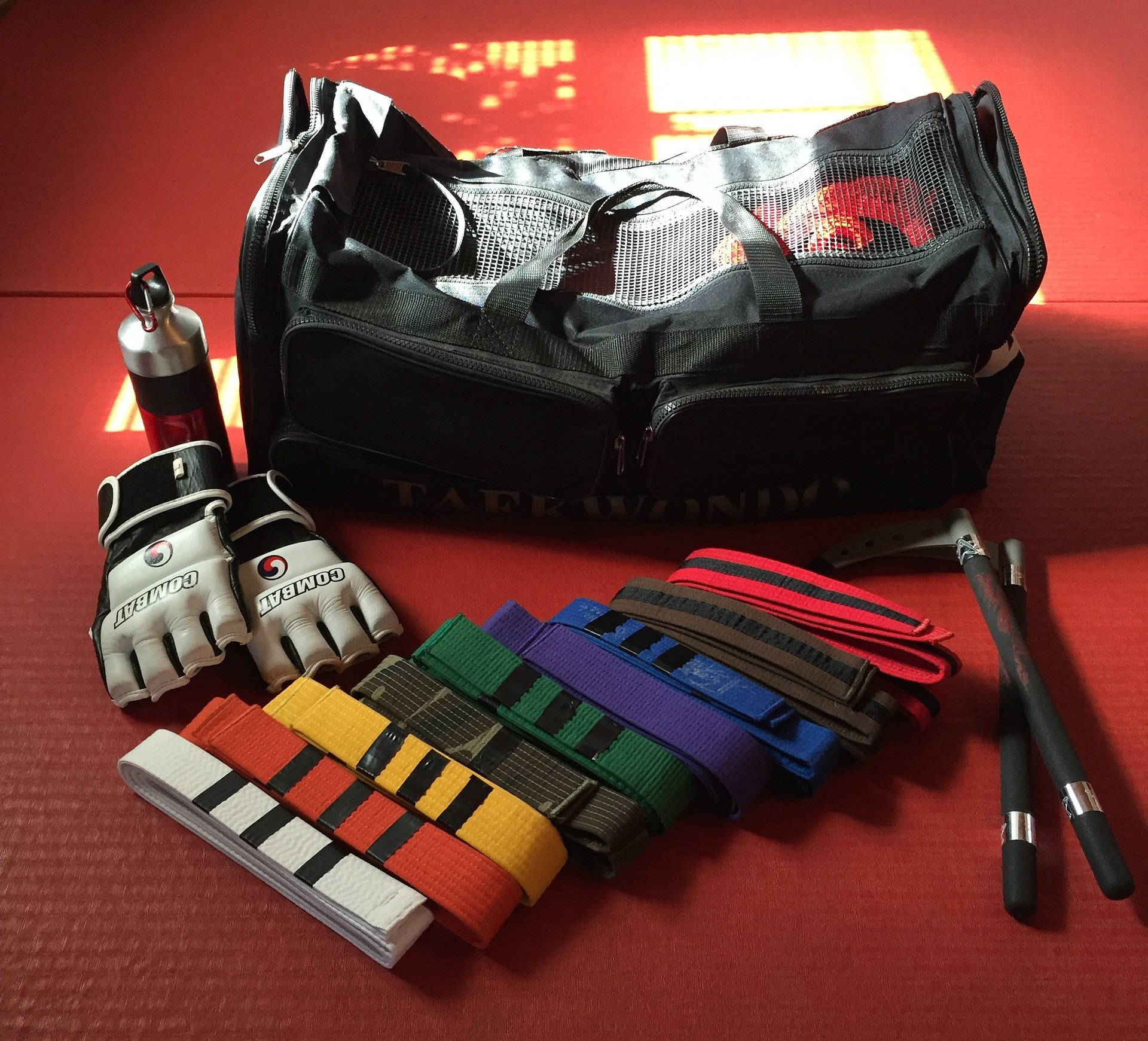Various colored martial arts belts, sparing gear, and weaponry in front of a gym bag on red carpet